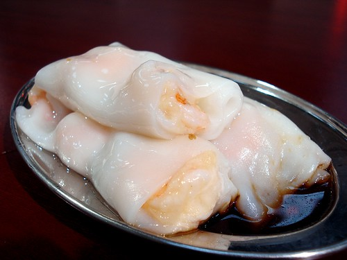 Three cheung fun rolls sit on a small oval metal plate.  Each roll consists of a thin, white, slippery rectangle of steamed rice-flour sheet, rolled up around some cooked king prawns.  A puddle of soy-sauce-based sauce sits underneath the rolls.