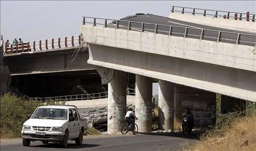 Un vehículo transita debajo de un puente que colapsó por Globovisión.