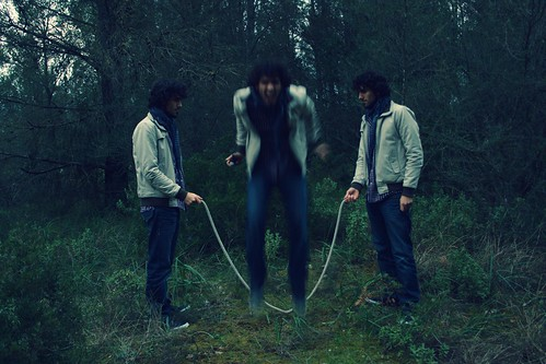 Jumping the jump rope in the forest with three identical clones
