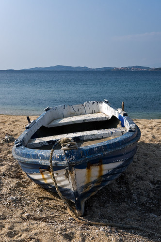Old rusty boat left to dry on the beach by Horia Varlan