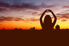 I'll light the sky with my heart. (dimplyemily) Tags: city pink blue shadow sky orange silhouette yellow night buildings lights evening hands heart