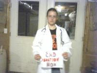 a blurry picture of a kid in a labcoat holding a homemade sign that says End Abortion Now