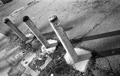 Fit it in the doldrums (QsySue) Tags: blackandwhite concrete graffiti parkinglot shadows pavement tag angles 35mmfilm pointandshoot barrier poles slap orangecounty gardengrove dtc olympusxa fomapan100 coupledrangefinder developedathome titleisaboniverlyric