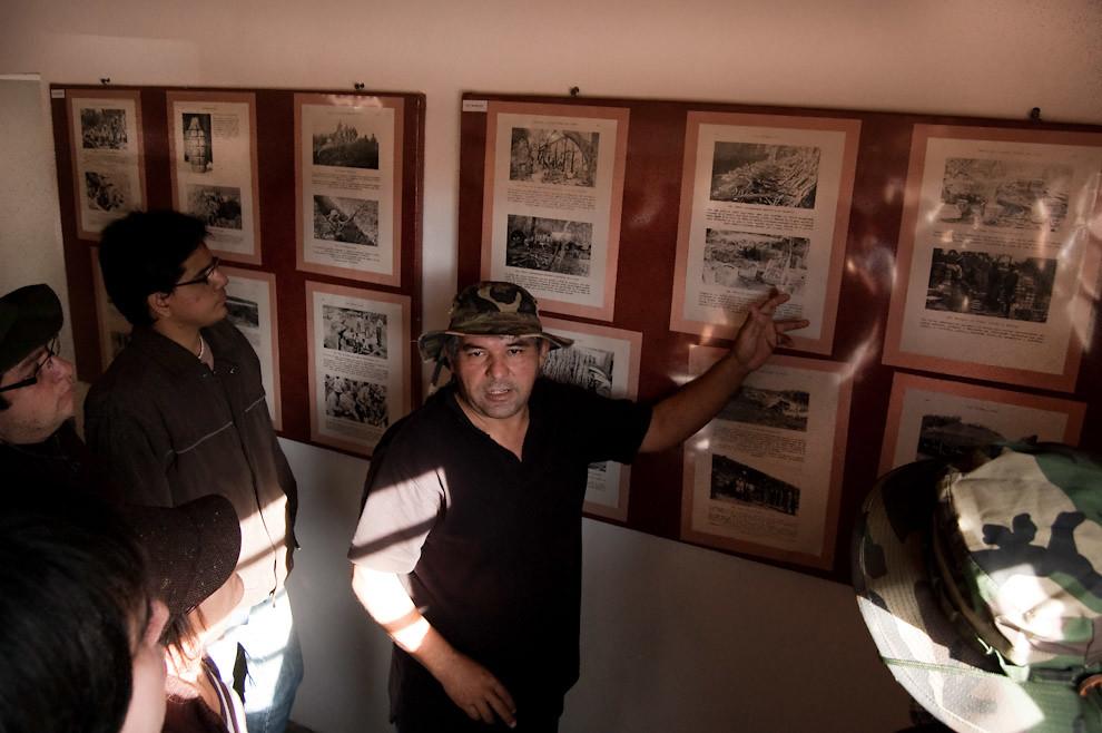Carlos Agüero explica a los visitantes las fotografías que se exhiben en el mural de fotos del Museo Histórico del Fortín Boquerón. (Elton Núñez - Fortín Boquerón, Paraguay)