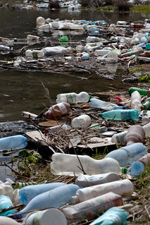 Plastic bottles and garbage on the bank of a river - if Nestle' Waters