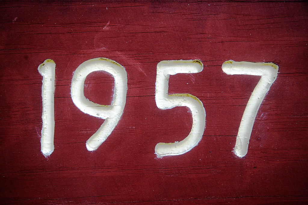 The number 1957 carved in a brownish-red wooden background.