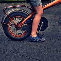 Taming the Bicycle (Remko.) Tags: street blue orange feet bike bicycle wheel foot kid blauw innocent kind hips taming marktwain oranje fiets crocs voet straat voeten remko onschuldig flickrgolfclub greatshortstory