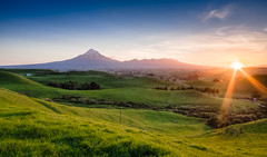 Taranaki Haze (Mark Solly (F-StopNinja)) Tags: sunset sky sun mountain grass silhouette farm country hill ranges rays hillside taranaki mtegmont sigma1020mm mttaranaki explored nikond90 marksolly