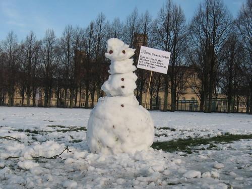 """Schnemann vor der Uni mit Schild """"Viel Spaß, 2010 – Das ist nicht der Winter aller Tage, ich streike nochmal keine Frage."""""""