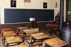 Historic Adventist Village by battlecreekcvb, on Flickr - old fashioned classroom, view facing chalkboard with 2 rows of wooden desks next to a wood stove