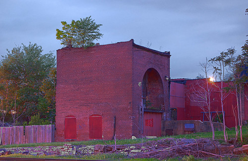 Brick building with large arched doorway, in the Carondelet neighborhood of Saint Louis, Missouri, USA - view at dusk