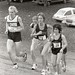 Katie Webb runs uphill during a cross-country meet, 1981? - 1984?