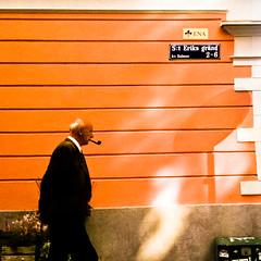 man with pipe (Georgios Karamanis) Tags: street flowers shadow people orange man wall square sweden uppsala 3gs ena iphone karamanis steriksgrnd