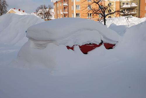 En insnöad bil stpr bortglömd på parkeringen