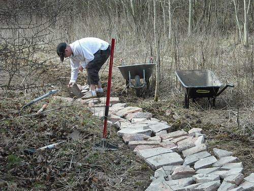 Arranging paving slabs as base material of a mountain bike track in Swindonl.