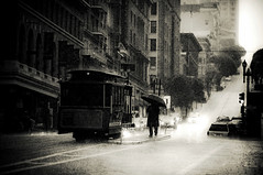 Rain (navid j) Tags: sf sanfrancisco california city blackandwhite bw white black wet rain umbrella hill rainy figure cablecar unionsquare downpour