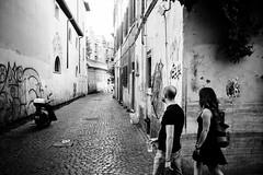 Chaising (lorenzoviolone) Tags: bw black white candid finepix fuji x100s fujifilm ilford pan f plus monochrome rni films cobblestone following mirrorless strangers streetphoto streetphotobw streetphotography walk:rome=june292017 walking blackwhite blackandwhite fujix100s fujifilmx100s ilfordpanfplus rnifilms roma lazio italy
