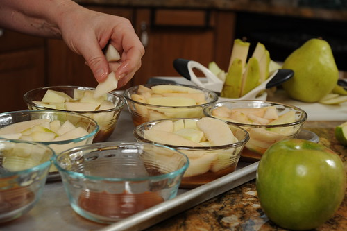 Layering the apple and pear slices in the cup on top of caramel