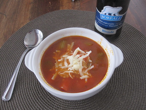 Vegetable soup with cheese and a beer