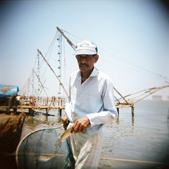 Look what I caught (maritahv) Tags: india fish 6x6 analog square holga fisherman velvia50 underskogno fortkochin april2010 chinesefishingtechnic