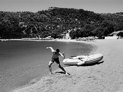 Martin is amazed to throw stones at sea. (panoskaralis) Tags: play game funny fun seascape bluesea seafront sealife sea seaside summer greeksummer summerholidays holidays blackwhite bw tree trees umbrela waterfront water watersport swimming island aegean aegeansea lesbian lesbos lesvosisland lesvos olivetrees outdoor landscape greece greek hellas hellenic