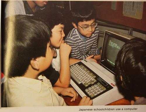 Niños japoneses programando trabajando con un ordenador en los 80