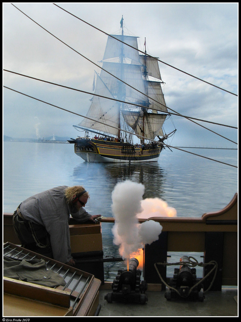 a cannon in the act of firing from the deck of Hawaiian Chieftain onto Lady Washington