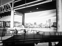Summer Pedal By The River (TMimages PDX) Tags: iphoneography photography image photo photograph streetscene fineartphotography geotagged people urban city streetphotography portland pacificnorthwest pedestrians buildings blackandwhite monochrome vignette bicycles biking waterfront river skyline bridge water summer