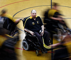 A bearded man in an electric wheelchair on a court, holding a hockey stick in his hand. People in wheelchairs are whizzing around him, blurred from movement.