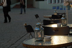 Passers by (halifaxlight (mostly off)) Tags: street sunlight norway walking cafe candles chairs empty vacant tables lanterns pedestrians bergen marken ashtrays hurried