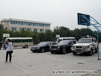 The lux cars from our entourage, parked at the school basketball court