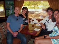 my daughter, son in law and granddaughter and me sitting in a booth on the wine train in wine country in california