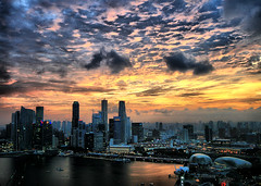 Stormy Sunset - Singapore (` Toshio ') Tags: city light sunset cloud sun storm reflection water architecture clouds buildings harbor singapore asia cityscape stormy esplanade durian cbd hdr highdynamicrange centralbusinessdistrict toshio singaporeflyer