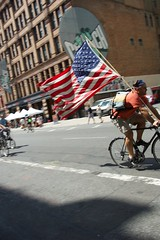 A guy riding his bike with a tattered U.S. flag as seen on Lafayette Street during Summer Streets. (jackszwergoldarchives) Tags: manhattan newyorkcity summerstreets szwergold