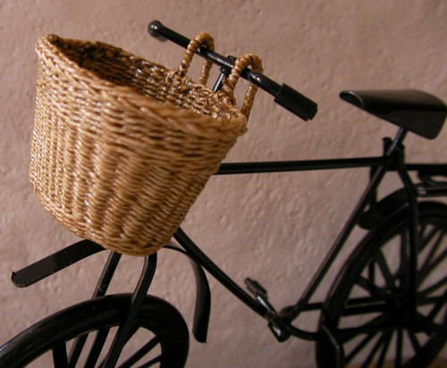 One of a kind, woven bicycle basket in 1:12 scale is hand made by CDHM Artisan Lidi Stroud, IGMA Artisan of Nambucca's Little Shoppe