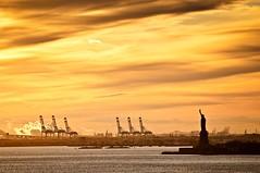 Mrs. Liberty welcomes the goods (dani.Co) Tags: sunset usa newyork yellow america puerto liberty harbor nikon harbour amarillo import ocaso export comercio estadosunidos nuevayork d300 materiales estatuadelalibertad 70200f28 importacin materias fpg bej platinumphoto anawesomeshot danico exportacin