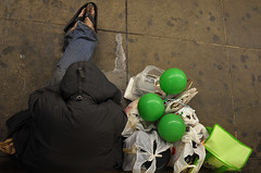three green balloons (zzombiekitty) Tags: nyc man green feet balloons subway sitting coat homeless platform rockefellercenter dirty fromabove stuff flipflops bags lookingdown asleep