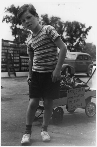 A Member of the Washington, D. C. Boys Club Wheels in a Load of Old Sneakers and Arctics to Add to the Nation's Scrap Rubber Collection. ca. 06/1942