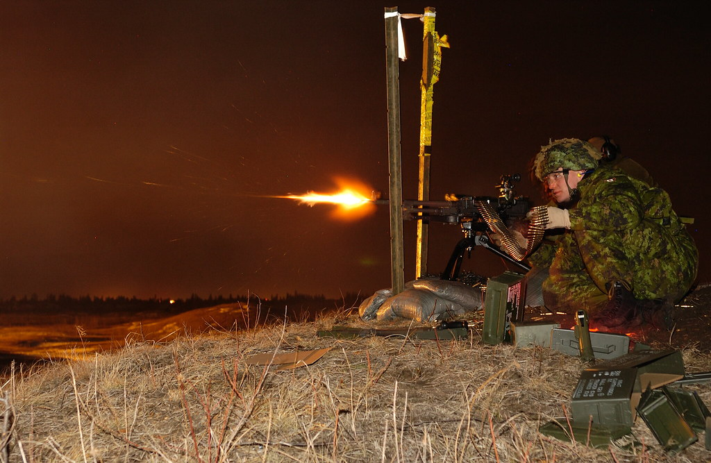 Corporal Nathan Coveney shoots live rounds with a C6 GPMG during night training