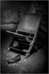 Chair scene at Eastern State Penitentiary (ronnymariano) Tags: chair abandoned easternstatepenitentiary history shoe stone prison 2017 museum sitting outdoors old rundown light woodmaterial dark everypixel weathered obsolete seat cultures blackandwhite retrostyled antique oldfashioned cell bnw monochrome
