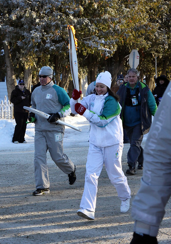 Michelle Arseneault carries the Olympic torch on the final leg of its journey.