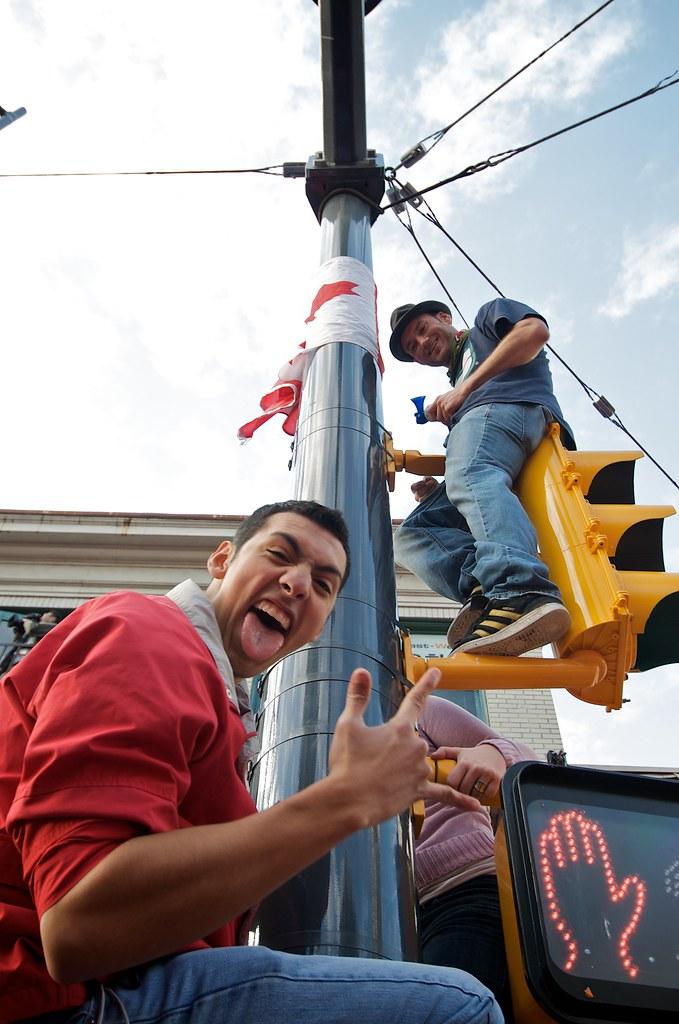 Fans Climb Street Lights