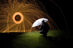 raining fire (cover of darkness) Tags: light portrait wool grass rain night umbrella self fire photography wire long exposure paint explore photograph raining spark