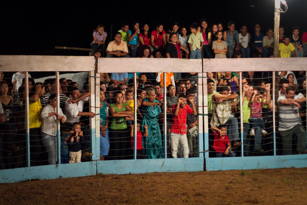 Publico de distintas edades, desde niños muy pequeños hasta la anciana del centro de la fotografía, miran con atención y se divierten de las piruetas realizadas por los toreros.   (15 de Agosto, Paraguay - Tetsu Espósito)