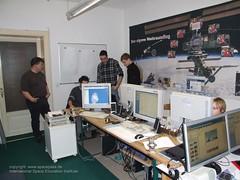 drei Leute stehn um jemanden, dem mit dem Computer arbeitet