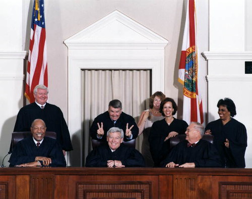 "Harry Anstead putting ""rabbit ears"" on Charles Wells prior to formal en banc portrait of Florida Supreme Court Justices from the year 2000"