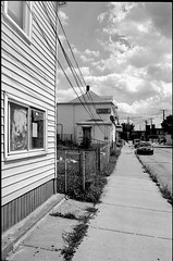 (Jeremy Whiting) Tags: analog 35mm black white monochrome city urban cityscape hamtown michigan detroit scan negative street streetscape liquor houses clouds sidewalk perspective vanishing point neighborhood summer daze canon kodak 400 full frame sky buildings hamtramck weeds siding