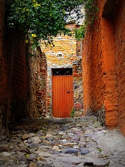 rough going (msdonnalee) Tags: door brick home mexico casa puerta alley stones dom entrance cobblestones adobe porta mexique porte portal entry mexiko doma woodendoor orangedoor rockypath photosfromsanmigueldeallende fotosdesanmigueldeallende photosbydonnacleveland mygearandmepremium