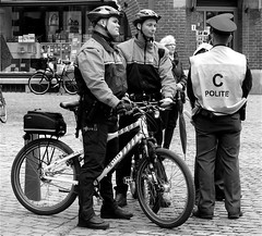 HANGING AROUND (Akbar Simonse) Tags: street people urban bw holland netherlands bike bicycle zwartwit candid streetphotography police denhaag thehague fiets helmets streetshot straat politie helmen straatfotografie straatfoto hofstijl akbarsimonse