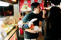So you're hungry but you can't possibly put your Schnauzer down, it may spoil his fancy dress (deepstoat) Tags: food night zeiss absurd taiwan schnauzer lazy spoilt contaxg2 kodakportra deepstoat